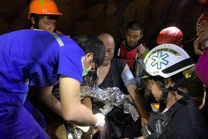 Thai rescue workers attending to Buddhist monk Phra Ajarn Manas in a partly-flooded cave yesterday. He was trapped after entering it days ago to meditate.