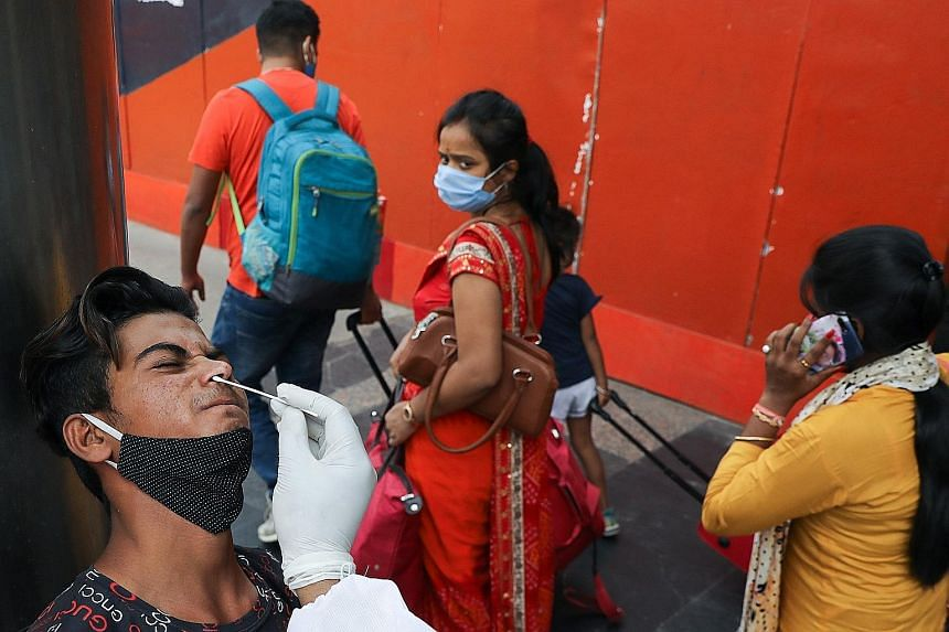 A man being swabbed by a healthcare worker at a railway station in New Delhi yesterday as the country battles a fresh wave of infections, recording almost 116,000 new cases in 24 hours.