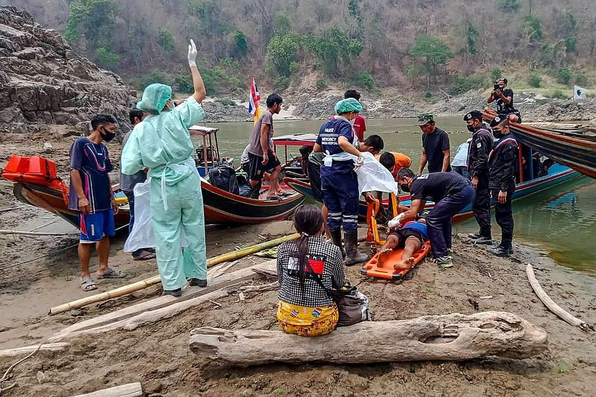 A handout photo from the Royal Thai Army on March 30 showing an injured Myanmar refugee being put on a stretcher before being taken to a hospital in Mae Sam Lap town after he crossed the Salween River while fleeing from air strikes in Myanmar's easte