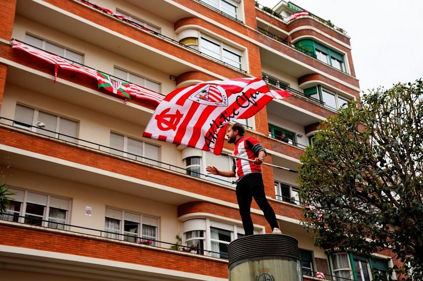In a photo taken on April 3, 2021, an Athletic Bilbao fan waves a flag ahead of their Copa Del Rey (King's Cup) final against Real Sociedad, in Bilbao, Spain.