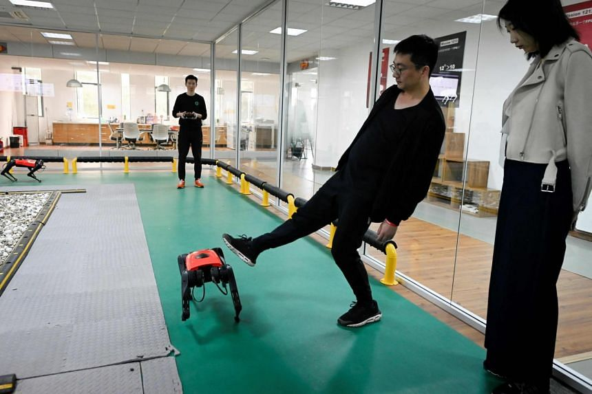 An employee using his foot to demonstrate the stability of an AlphaDog quadruped robot at Weilan Intelligent Technology Corporation in Nanjing, China, on April 2, 2021.