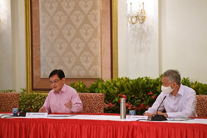 DPM Heng Swee Keat (left) speaking at a press conference with PM Lee Hsien Loong at the Istana on April 8, 2021.