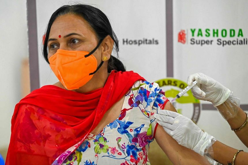 A medical worker inoculates a woman in India with the AstraZeneca vaccine.