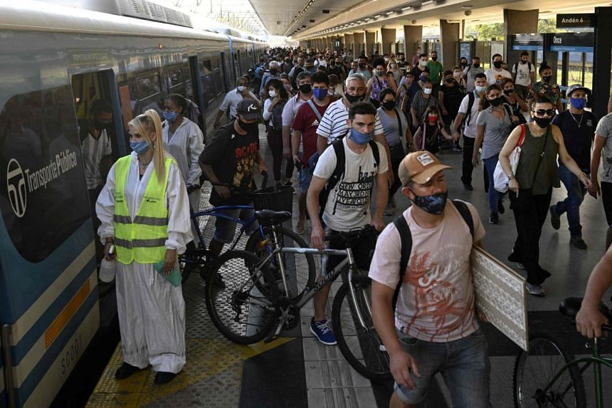 Passengers descend at the Once train station in Buenos Aires, on April 7, 2021.