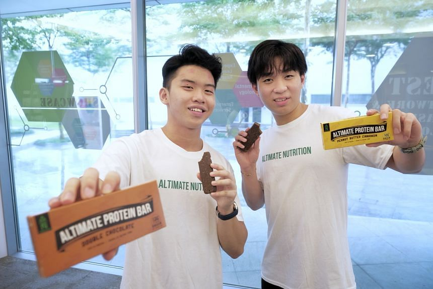 Republic Polytechnic students and Altimate Nutrition co-founders John Lee (left) and Gavriel Tan pose with their protein bars made with cricket flour, on April 6, 2021.