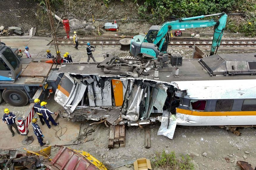 An aerial view shows workers checking damaged carriages at the site of a derailed train accident in Hualien, on April 6, 2021.