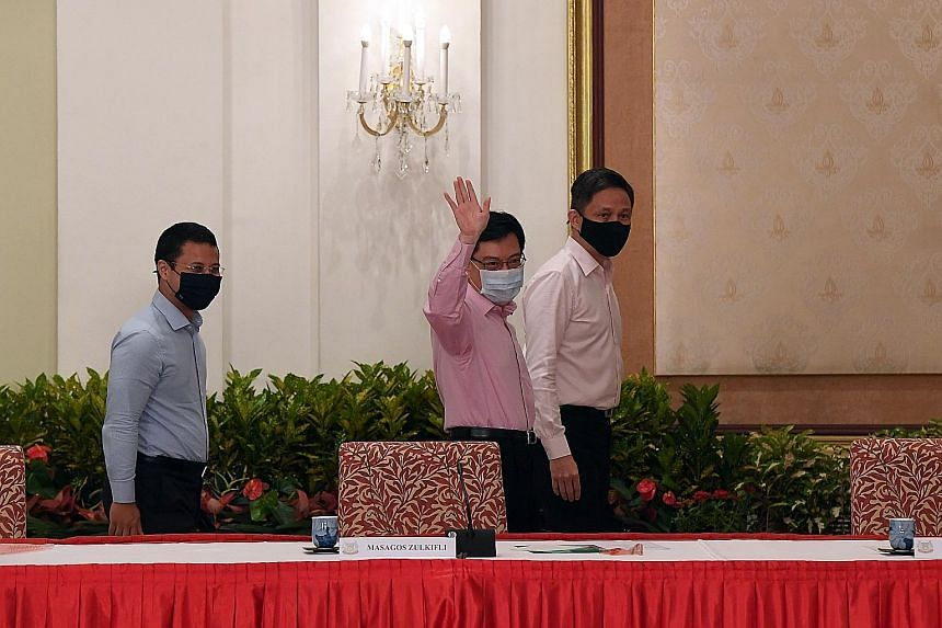 Deputy Prime Minister Heng Swee Keat, flanked by National Development Minister Desmond Lee (far left) and Trade and Industry Minister Chan Chun Sing, waving to the media after the news conference yesterday. ST PHOTO: DESMOND FOO