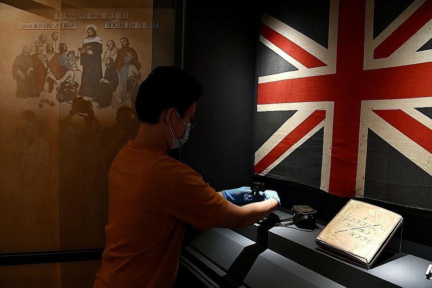 A worker installing a Kodak Baby Brownie camera for exhibition at the museum. It was hidden by Sergeant John Ritchie Johnston during his incarceration at the old Changi Prison. ST PHOTOS: DESMOND FOO The old number plate from cell 14 of the old Chang