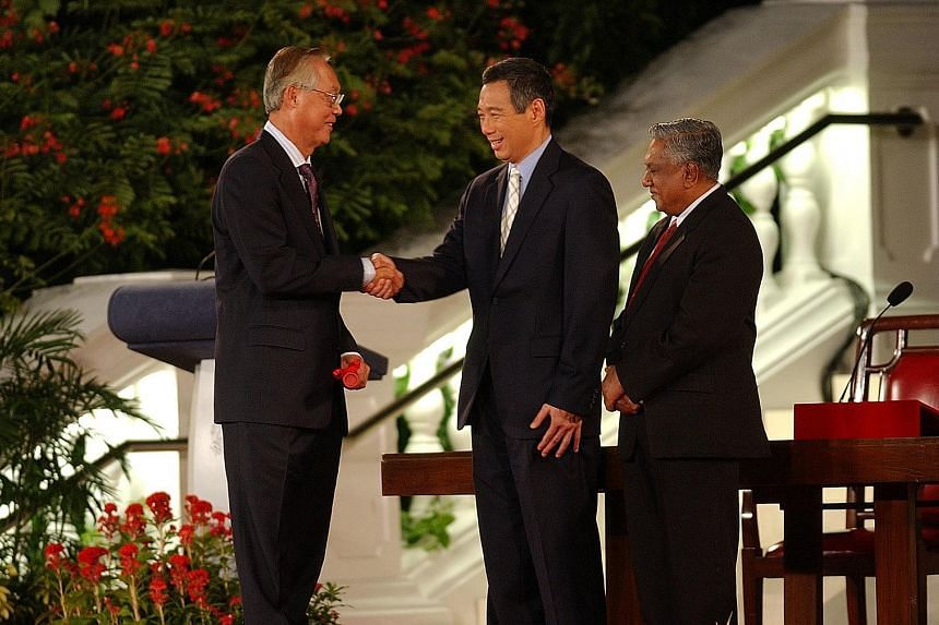 Above: Newly sworn-in Prime Minister Lee Hsien Loong shaking hands with Mr Goh Chok Tong, Singapore's second PM, on Aug 12, 2004, as then President S R Nathan looked on. Left: Prime Minister Goh waving to the crowd at the Padang after his swearing-in