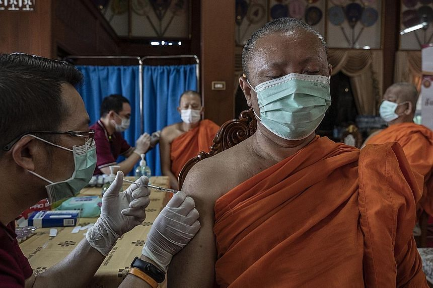 Thai monks receiving AstraZeneca's Covid-19 vaccine at a monastery in Bangkok on Wednesday. Reviews by British and European Union regulators have found potential links between the shot and rare blood clots. PHOTO: NYTIMES