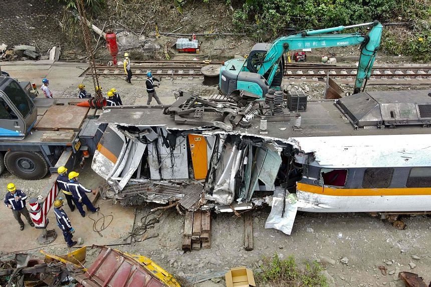 Workers at the train accident site on the mountains of Hualien in eastern Taiwan on Tuesday. The truck involved in the crash allegedly tumbled down to the train tracks after getting caught in vegetation, but the Taiwan Transportation Safety Board is