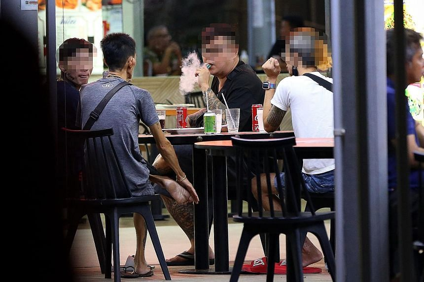 Top: E-vaporiser users openly puffing away at a coffee shop in Woodlands. Above: Dr Aneez Ahmed, who has operated on vapers suffering from collapsed lungs, says that even when there is no nicotine involved, inhaling the mist from e-vaporisers may dam