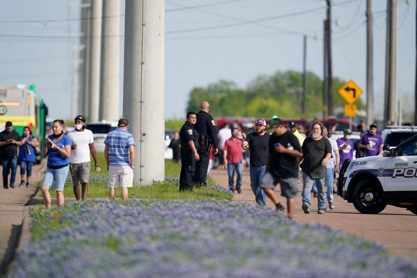 Bryan police officers direct workers away from the scene of a mass shooting at an industrial park in Bryan, Texas on April 8, 2021.