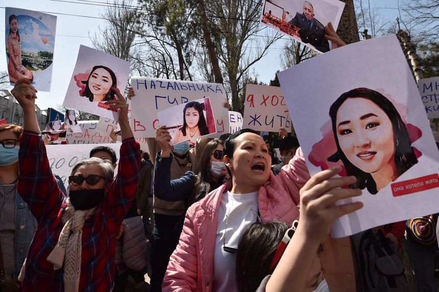 People hold pictures as they attend a rally for women's rights protection in Bishkek, on April 8, 2021.