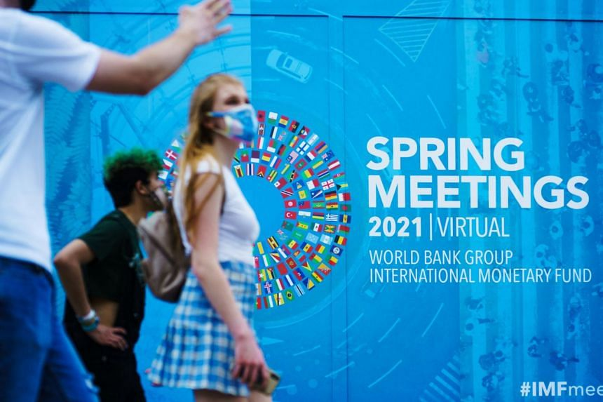 People pass by a banner for the World Bank Group/International Monetary Fund Virtual Spring Meetings in Washington, on April 7, 2021.