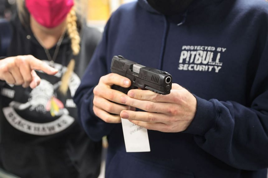 A customer shops for a new handgun at Freddie Bear Sports on April 8, 2021, in Tinley Park, Illinois.