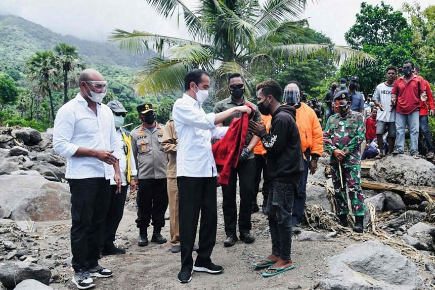 Indonesian president Joko Widodo giving his jacket to a survivor on Lembata Island, in Indonesia, on April 9, 2021.