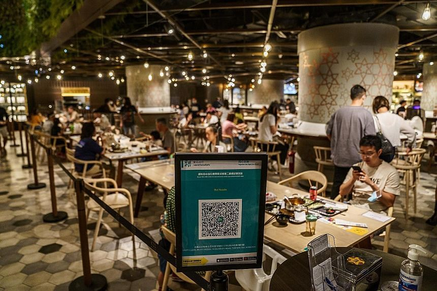 A QR code for a contact-tracing app in a Hong Kong foodcourt. Over 700,000 doses of the Covid-19 vaccine have been administered to the city's 7.5 million population but CEO Carrie Lam finds the figure unsatisfactory. The slow take-up rate is due main