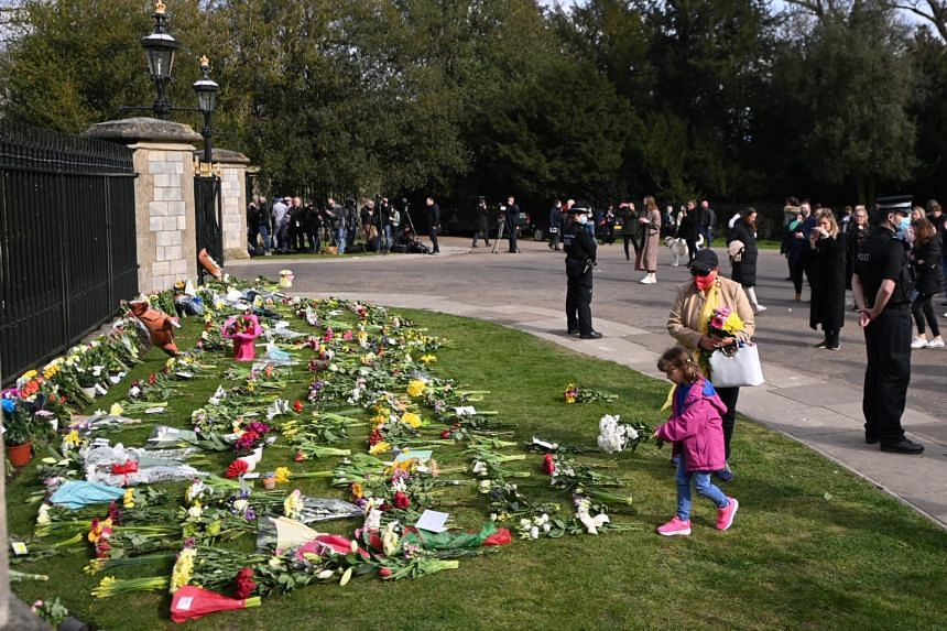People place flowers with condolence messages outside Windsor Castle following the passing of Britain's Prince Philip, Duke of Edinburgh, in Windsor on April 9, 2021.