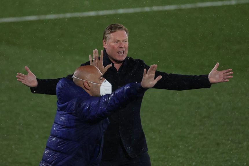 Barcelona's Koeman (right) reacts during the match against Real Madrid.