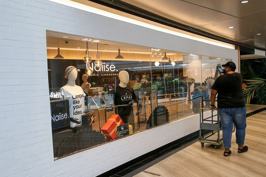 An employee of a vendor going to collect shelves at the Naiise outlet at Jewel Changi Airport on April 10, 2021.