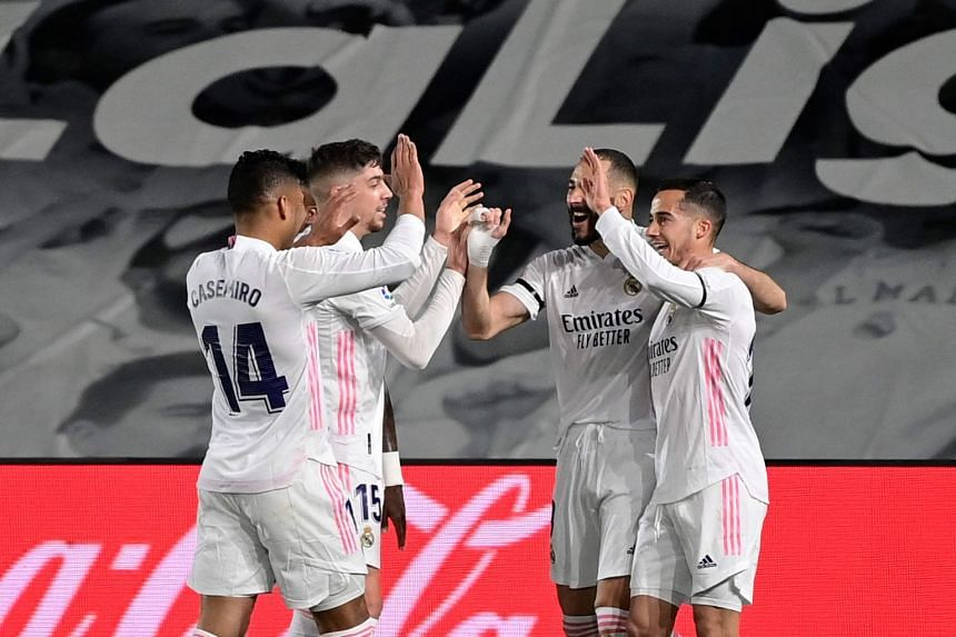 Real Madrid's French forward Karim Benzema (second right) celebrates with teammates after scoring.