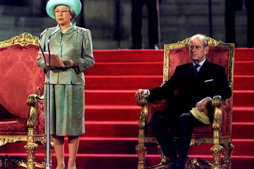 In a photo taken on May 5, 1995, Prince Philip watches as Queen Elizabeth delivers an address at the Palace of Westminster.