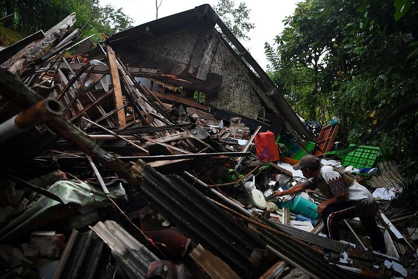 Residents examining the damaged wall of a house in Malang on Saturday. A resident salvaging his belongings from his house in Lumajang regency, in East Java province, yesterday. A man cleaning up a courtroom that was damaged in Saturday's earthquake i