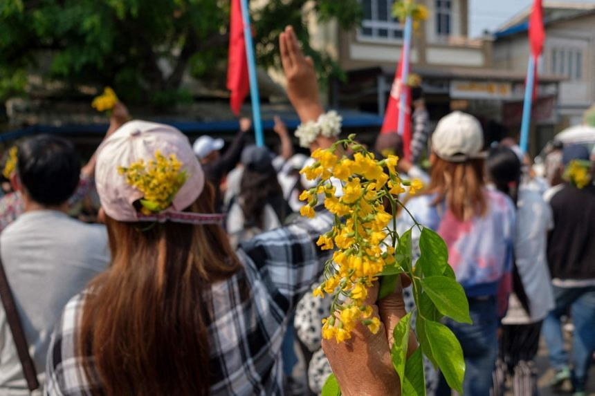 Protesters with padauk flowers, which usually bloom during Myanmar's traditional New Year, in Mandalay on April 7, 2021.