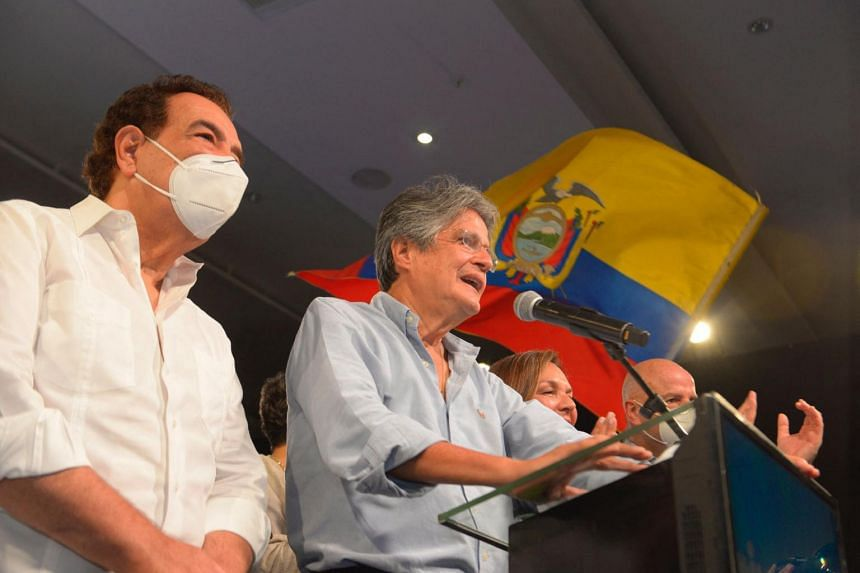 Ecuadorean presidential candidate Guillermo Lasso (right) speaks to the press as he celebrates his victory, on April 11, 2021.