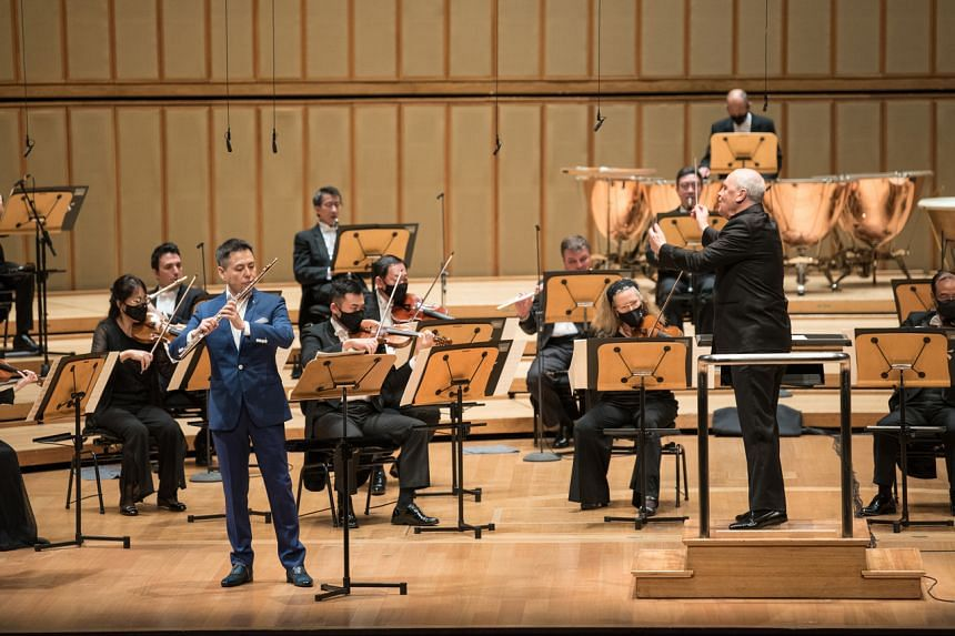 Singapore Symphony Orchestra's principal flute Jin Ta (in blue suit) and SSO's chief conductor Hans Graf (on the podium) in Flurry Of The Flute.