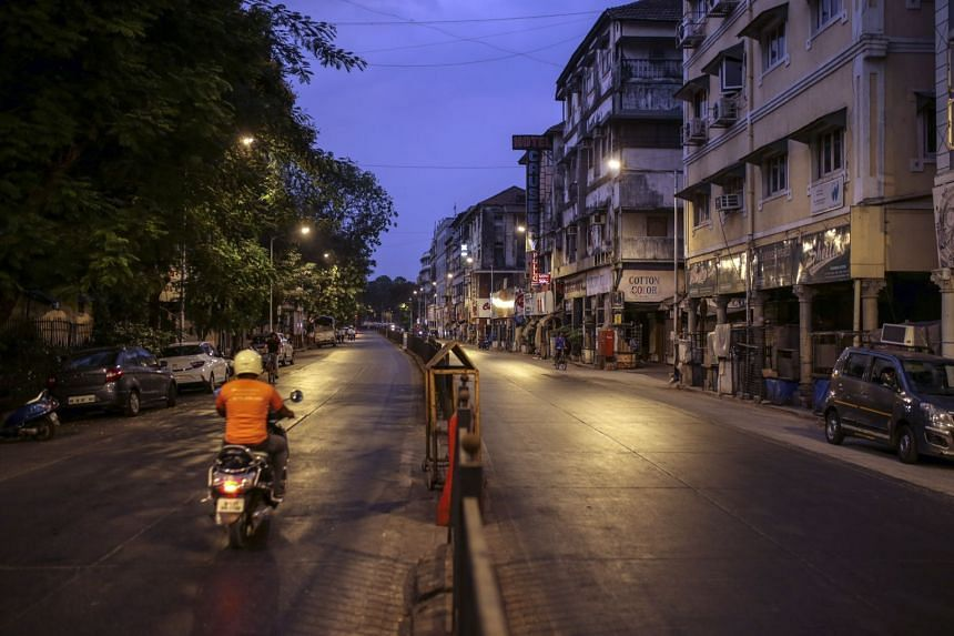 A motorcyclist riding past shuttered stores in Mumbai at the weekend amid a lockdown.