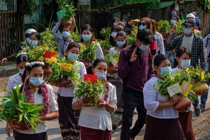 Demonstrators carrying traditional Thingyan pots filled with flowers in Mandalay on April 13, 2021.