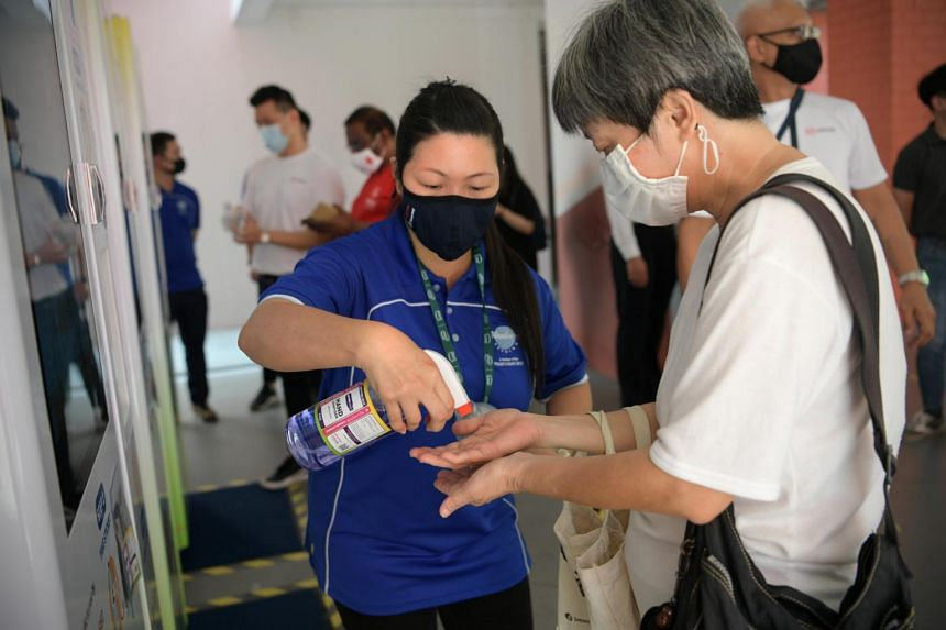 Vending machine assistant Tang Li Ring, 44, letting a resident try out the zero-alcohol sanitiser in Choa Chu Kang on April 12, 2021.