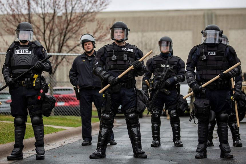 Minnesota police officers stand guard outside the Brooklyn Centre police station in Minneapolis, on April 12, 2021.