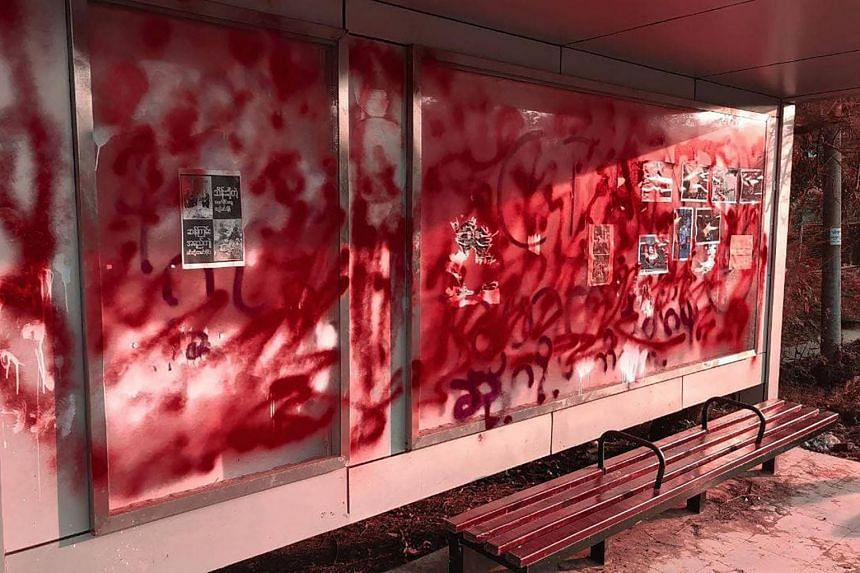 "A bus stop covered in red spray paint as part of a ""bleeding strike"" demonstration against the military coup in Yangon."