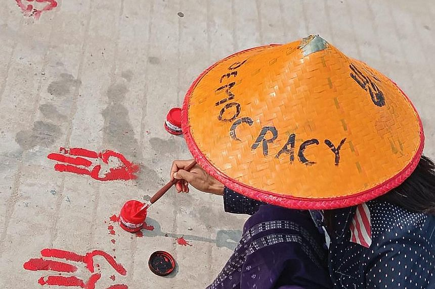 """This photo, posted on Facebook and shared by an anonymous source yesterday, shows a protester painting the three-finger salute symbol on the ground with red paint as part of a """"bloody paint strike"""" protest against the military coup in Shwebo, Myanmar"""