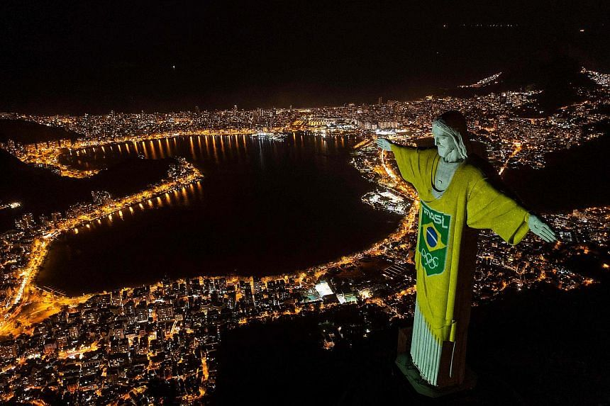 Aerial view of the statue of Christ the Redeemer illuminated with the Brazilian flag colours and Olympic arrows in Rio de Janeiro, on April 14, 2021.