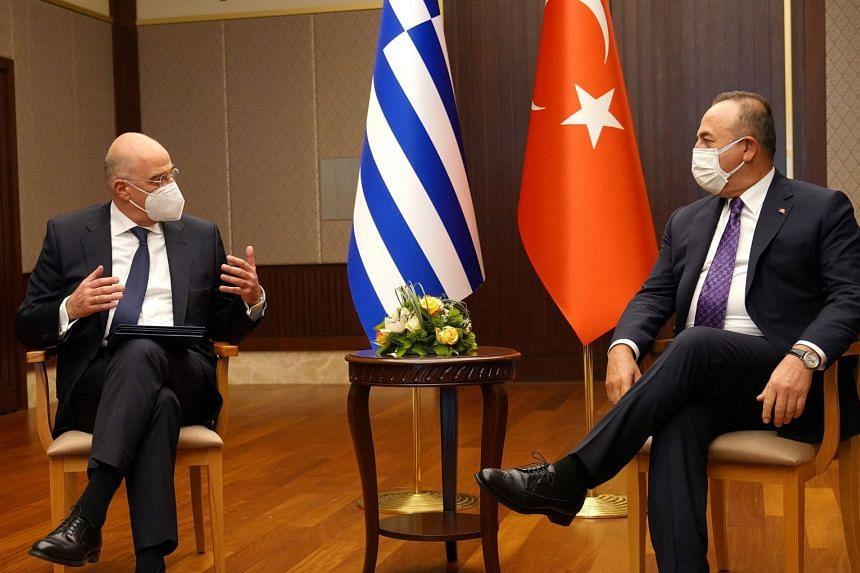 Greek Foreign Minister Nikos Dendias (left) talks to his Turkish counterpart Mevlut Cavusoglu during a meeting in Ankara, on April 15, 2021.