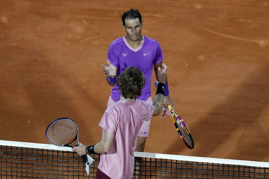 Nadal (facing) shakes hands with Andrey Rublev of Russia after losing their quarter final match.
