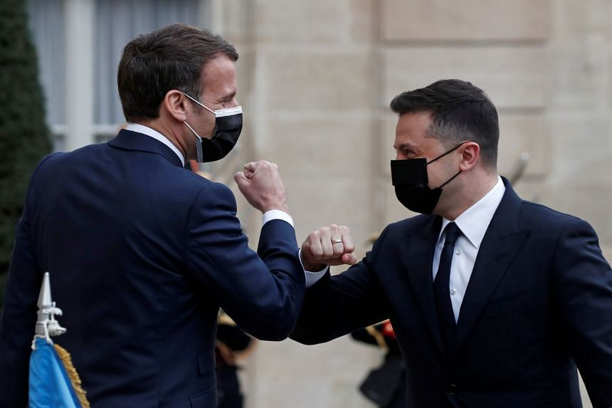 French President Emmanuel Macron elbow bumps with Ukraine's President Volodymyr Zelenskiy as he arrives at the Elysee Palace in Paris.