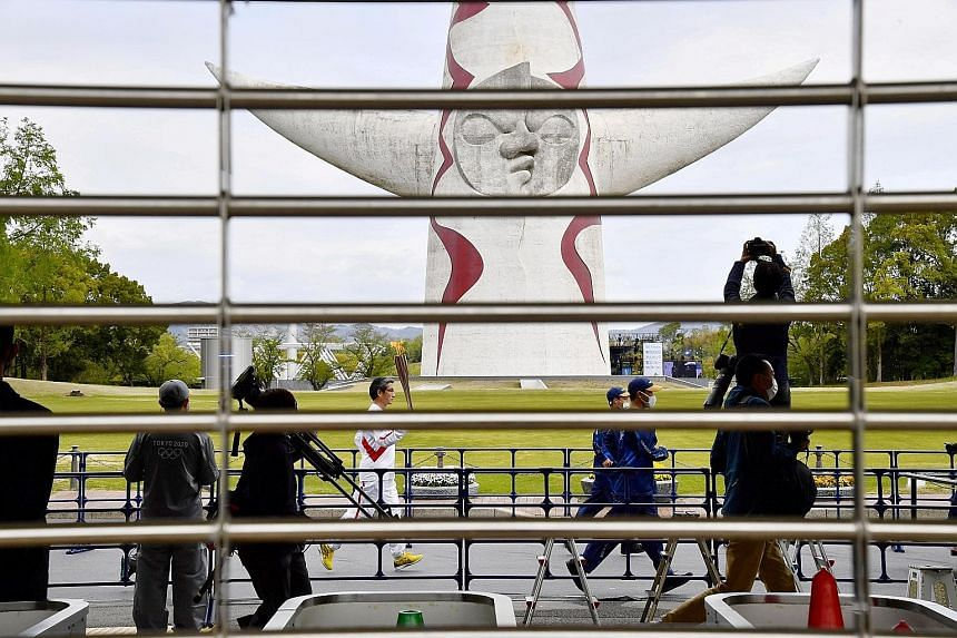 """A Tokyo Olympics torch relay runner at the Expo '70 Commemorative Park in Osaka on Tuesday. Experts are warning that the Games are at risk of going down in history as a """"super-spreader"""" event."""