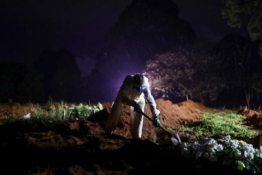 A gravedigger wearing a protective suit as he prepares for a night burial at Vila Formosa cemetery in Sao Paulo, Brazil on March 30, 2021.