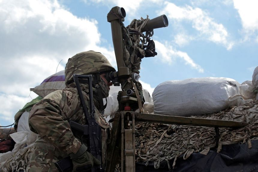 A service member of the Ukrainian armed forces observes fighting positions on the line of separation near the rebel-controlled city of Donetsk, Ukraine, on April 17, 2021.