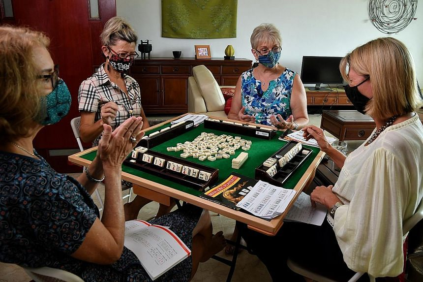 Ms Vishali Midha (above centre) invited her friends from the American Women's Association for a Holi-themed mahjong session. (Above) Handwritten notes and guidebooks on mahjong help Anza Mahjong Group members pick up the game. (Right) In Western-styl