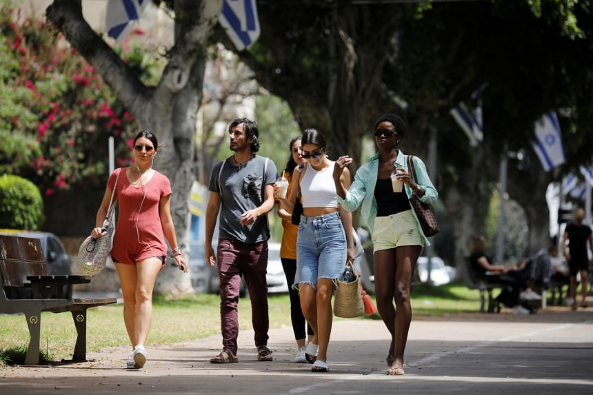 Pedestrians walking along a boulevard in Tel Aviv after Israel rescinded the mandatory wearing of masks outdoors, on April 18, 2021.