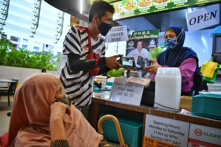 (From left) Madam Salmah Ahmat and her son, Mr Muhammad Azaman using an E-Card to redeem a free meal at Kampung Admiralty Hawker Centre on April 18, 2021.