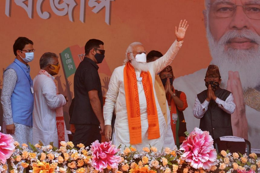 PM Narendra Modi (centre) waves to supporters in a rally meeting during at Kawakhali on the outskirts of Siliguri, on April 10, 2021.