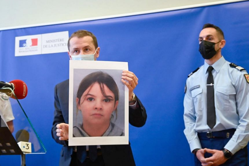 In a photo taken on April 14, 2021, public prosecutor Nicolas Heitz (centre) holds a portrait of Mia Montemaggi during a press conference.