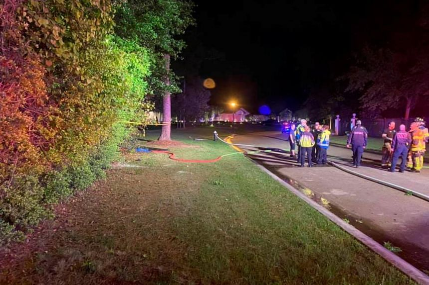 Emergency services personnel stand near the site of a Tesla vehicle crash in The Woodlands, Texas, on April 17, 2021.